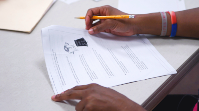 A GED student works on a packet