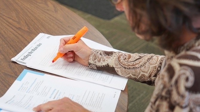 A Seeds of Literacy tutor grades a student's work.