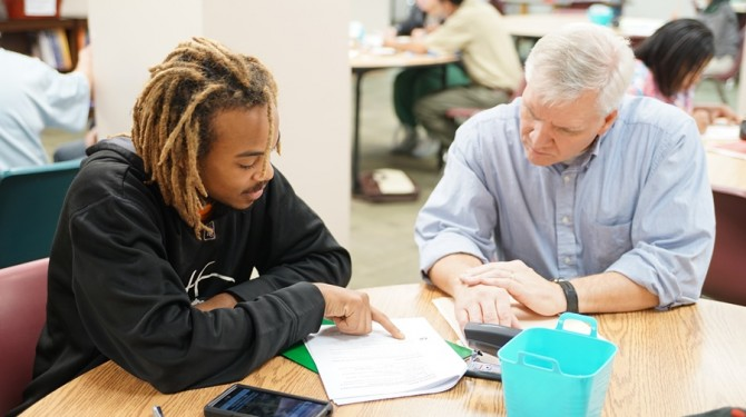 A tutor helps an evening GED student.