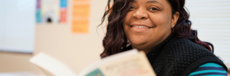 A GED student reads a book at Seeds of Literacy