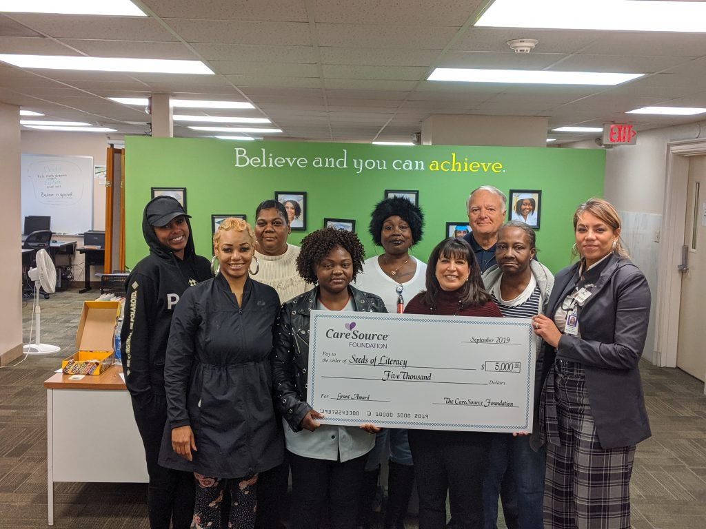 CareSource Community Marketing Representative Eliduvina Aponte, far right, presented a ceremonial $5,000 check to Seeds of Literacy President and CEO Bonnie Entler, Chairman of the Board George Miller and several Seeds of Literacy students at Seeds West, 3104 W. 25th St. in Cleveland, on Nov. 14.